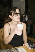 A woman sitting at a cafe holding a cup of coffee Stock Photos