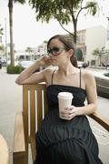A woman sitting at a sidewalk cafe holding a cup of coffee - stock photo