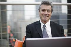 Businessman sitting on a rooftop and working on a laptop - stock photo