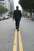 Businessman walking along dividing line on a city street Stock Photos