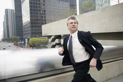 Businessman running along a walkway in the financial district Stock Photos