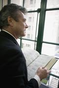 Businessman standing by a window holding a book Stock Photos