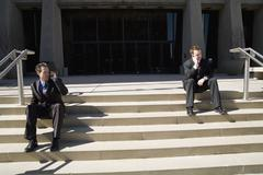 Two businessmen on the steps using mobile phones in front of an office building Stock Photos