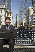 Businessman sitting on an outside bench using a laptop - stock photo
