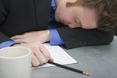 Young businessman asleep on a desk Stock Photos