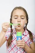 A girl blowing bubbles Stock Photos