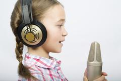 A girl wearing headphones and holding a microphone Stock Photos