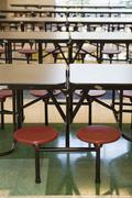 Rows of stools and tables in school canteen Stock Photos