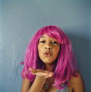 Teenage girl wearing a pink wig and blowing a kiss - stock photo