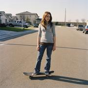Teenage girl standing on skateboard in the street Stock Photos