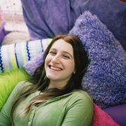 Stock Photo of Teenage girl lying between cushions smiling
