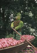 Flower man rowing a boat in an ornamental garden Stock Photos