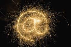 At' Symbol drawn with a sparkler Stock Photos