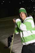 Stock Photo of Young man standing on a ski slope with a snowboard