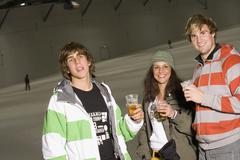 Three friends standing on a ski slope and drinking beer Stock Photos