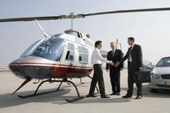 Businessmen shaking hands by a helicopter - stock photo