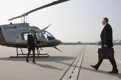 Businesswoman greeting a businessman by a helicopter - stock photo
