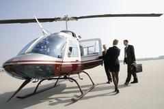 Woman assisting businessmen board a helicopter Stock Photos