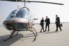 Businesswoman greeting two businessman by a helicopter - stock photo