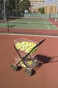 A trolley full of tennis balls at the edge of a tennis court Stock Photos