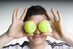 Mies tilalla kaksi tennispallot edessä hänen kasvonsa Kuvituskuvat
