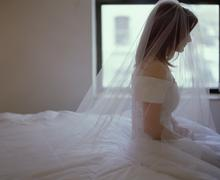 A bride sitting on a bed - stock photo