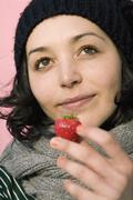 A woman holding a strawberry Stock Photos