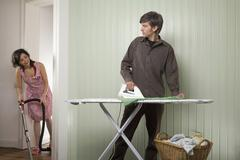 A young couple doing housework - stock photo
