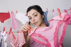 A woman hanging underwear on a clothesline Stock Photos
