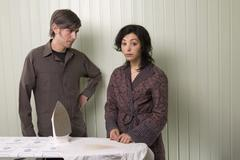 A man and a woman standing next to a burnt shirt on an ironing board Stock Photos