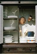 Cookwear and crockery in a cabinet Stock Photos