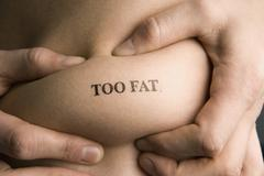 A man pinching part of his abdomen stamped 'Too Fat' Stock Photos