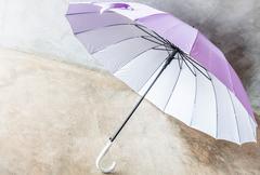 purple silver bronze uv protection umbrella on the floor - stock photo
