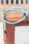 black hooks of blue rubber band on wood table - stock photo