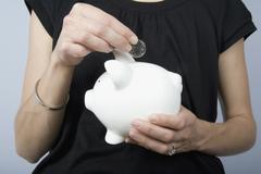 Detail of a woman holding a coin above a piggy bank Stock Photos