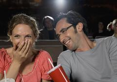 A mid adult couple laughing in a movie theater Stock Photos