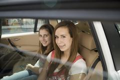 Two adolescent girls sitting in the back seat of a car - stock photo