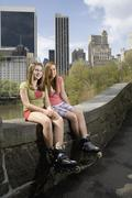 Two adolescent girls wearing inline skates and sitting on railing Stock Photos