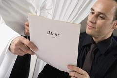 A waiter showing a man the menu - stock photo
