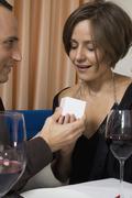 A man giving a woman a ring in a restaurant Stock Photos