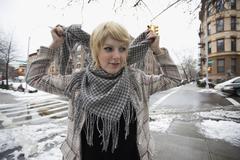 Nuori nainen laittaa huivi taas seisoo kadunkulmassa Kuvituskuvat