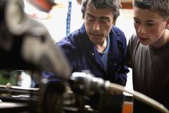A man training a young man in a printing factory Stock Photos