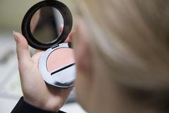 Detail of a woman holding a pressed powder compact Stock Photos
