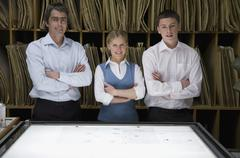 Three colleagues standing side by side behind a light box Stock Photos
