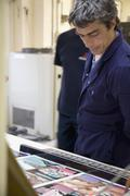A man looking at printed samples in a factory - stock photo