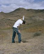 A man standing in an arid landscape and pouring water over his head Stock Photos