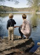 A mother and son feeding ducks by a lake Stock Photos