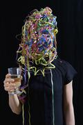 A woman covered in streamers and holding a glass of champagne Stock Photos
