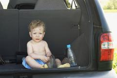 A young boy sitting in the back of an SUV Stock Photos