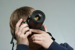 A young man taking a photograph - stock photo